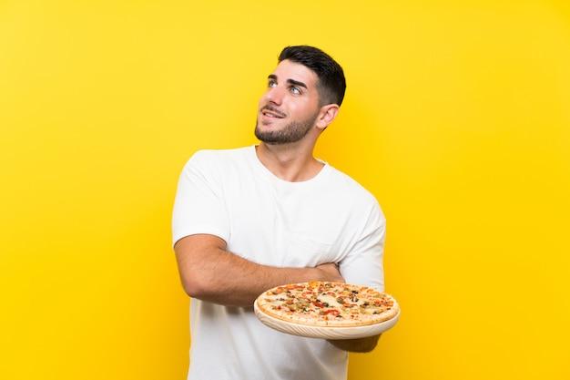 Молодой красивый мужчина держит пиццу на изолированной желтой стене, глядя вверх, в то время как улыбается