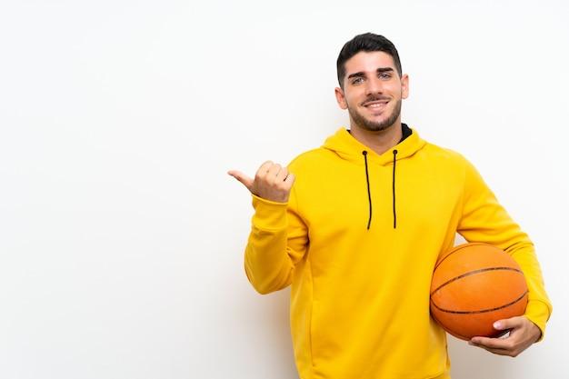 製品を提示する側を指している孤立した白い壁の上のハンサムな若いバスケットボールプレーヤー男