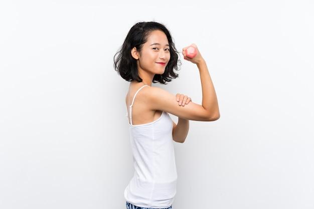 孤立した壁を越えて重量挙げを作る若いアジアの女の子