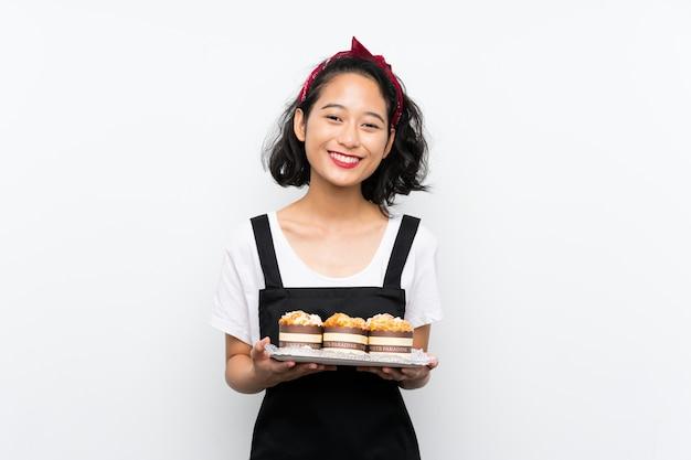 Молодая азиатская девушка держа много торта булочки над изолированной белой стеной усмехаясь много