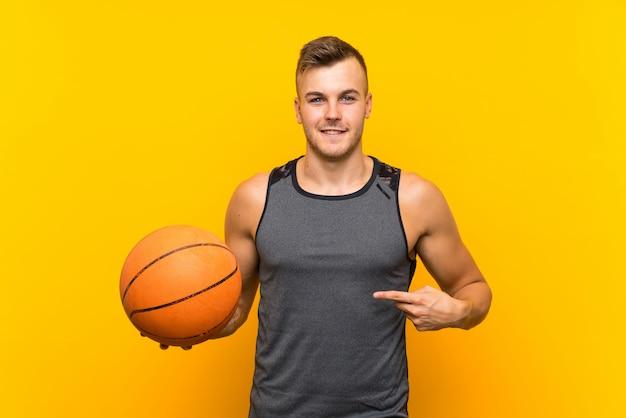 驚きの表情で孤立した黄色の壁にバスケットボールを置く若いハンサムな金髪男