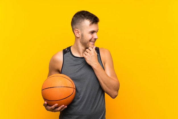 アイデアを考えて、側を見て孤立した黄色の壁にバスケットボールを保持している若いハンサムな金髪男
