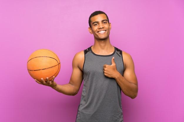 Молодой спортивный человек с баскетбольным мячом над фиолетовой стеной с большими пальцами вверх, потому что случилось что-то хорошее