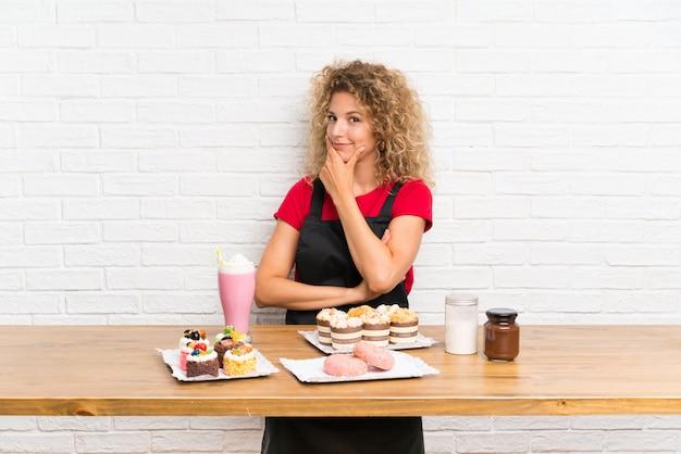 Молодая женщина с большим количеством различных мини-пирожных в таблице, думая, идея