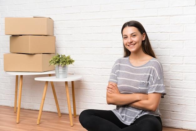 ボックスの間で新しい家に移動する若い女性