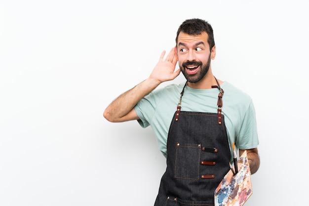 耳に手を置くことによって何かを聞いて孤立した壁にパレットを保持している若いアーティスト男