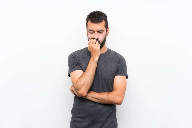 疑問を持つ孤立した白い壁の上の若いハンサムな男