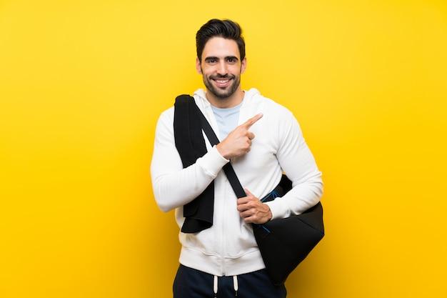 製品を提示する側を指している孤立した黄色の壁の上の若いスポーツ男