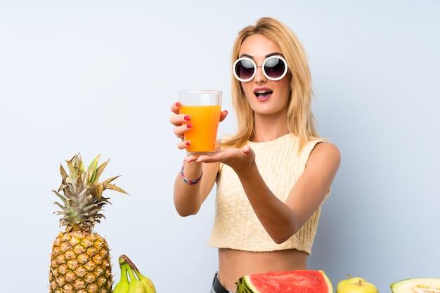 たくさんの果物を持つ若いブロンドの女性
