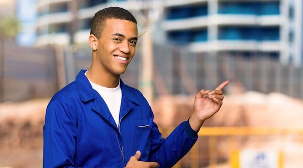 建設現場で横位置に側に指を指している若いアフロアメリカンワーカー男