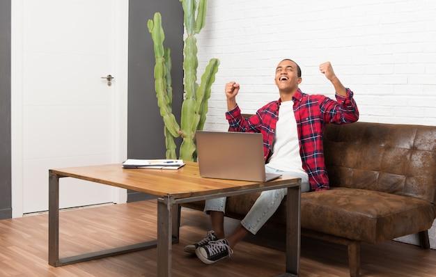 Афро-американский мужчина с ноутбуком в гостиной, празднует победу в позиции победителя