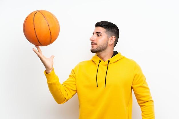 白い壁の上のハンサムな若いバスケットボールプレーヤー男