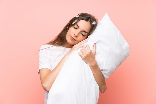 ピンクの壁の上のパジャマの若い女性