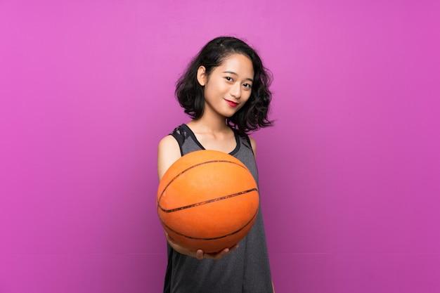 Молодая азиатская женщина играя баскетбол над фиолетовой стеной