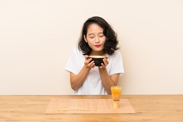 Молодая азиатская девушка с чаем матча