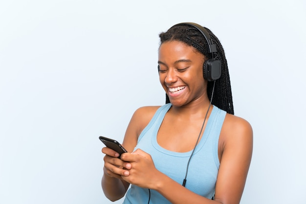 携帯電話で音楽を聞いて長い編み髪のアフリカ系アメリカ人のティーンエイジャーの女の子