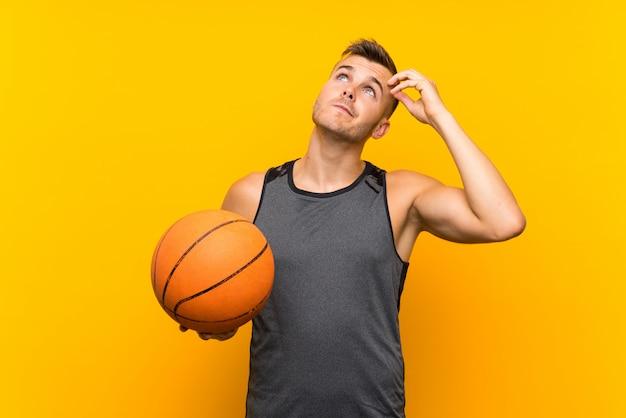 疑いがあると混乱の表情と黄色の壁の上のバスケットボールを保持している若いハンサムな金髪男
