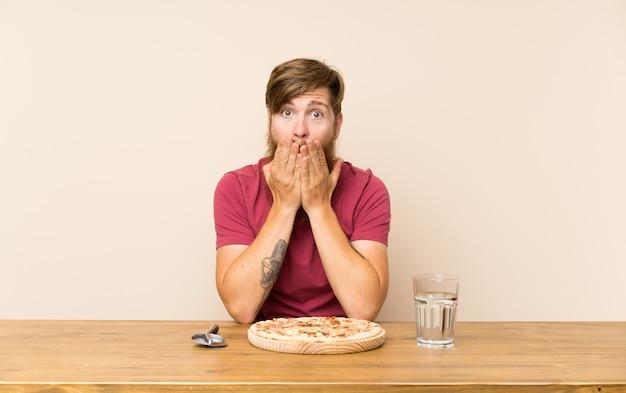 テーブルで長いひげと驚きの表情でピザと赤毛の男