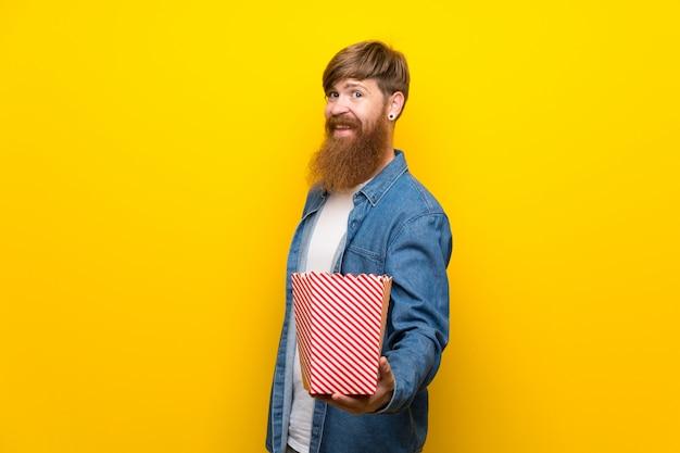 ポップコーンのボウルを保持している黄色の壁の上の長いひげを持つ赤毛の男