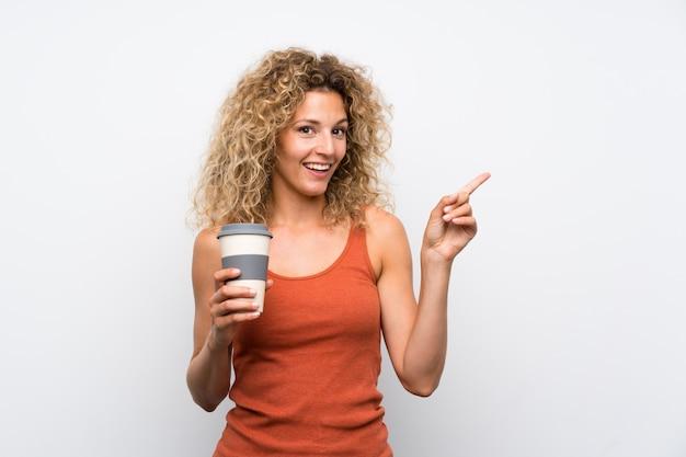 Молодая блондинка с вьющимися волосами, держа кофе на вынос, удивлен и указывая пальцем в сторону
