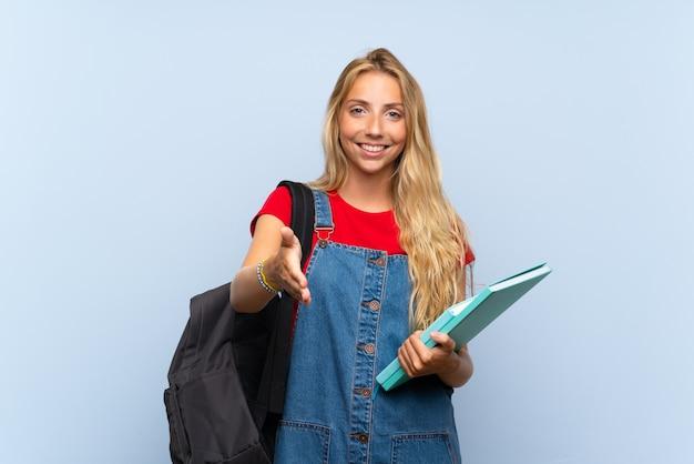 Молодая блондинка студентка над синей стеной рукопожатия после хорошей сделки