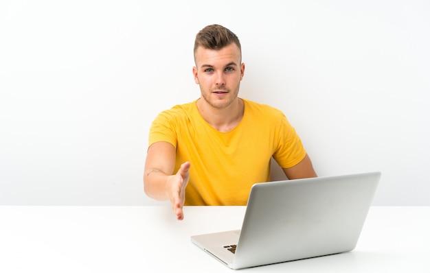 Молодой блондин человек в таблице с ноутбуком рукопожатие после хорошей сделки