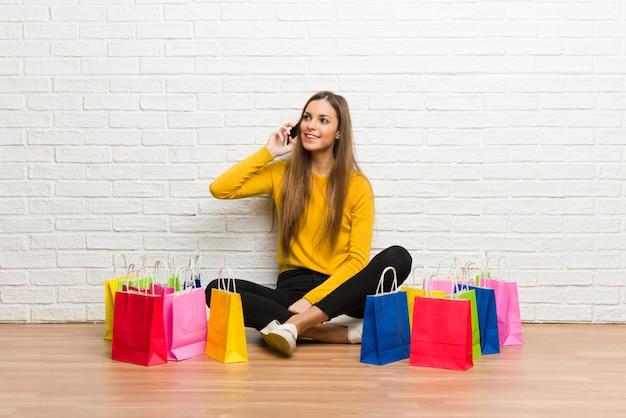 携帯電話との会話を維持する買い物袋の多くを持つ若い女の子