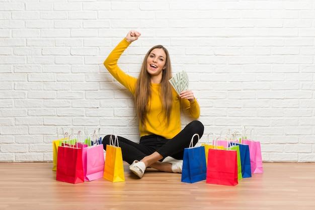 たくさんのお金を取って買い物袋の多くを持つ若い女の子