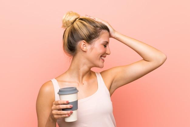 テイクアウェイコーヒーを保持している若いブロンドの女性は何かを実現し、解決策を意図