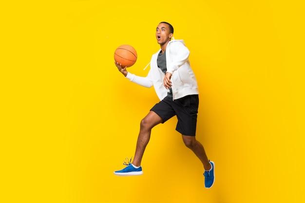孤立した黄色の壁の上のアフロアメリカンバスケットボールプレーヤー男