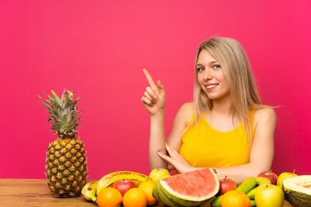 側に指を指している果物の多くの若いブロンドの女性