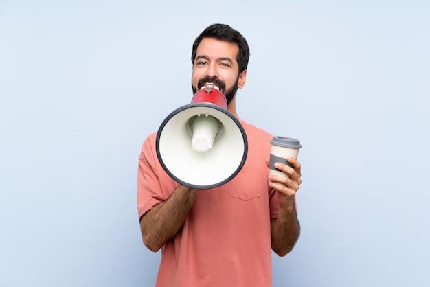 メガホンを通して叫んで孤立した青い壁にテイクアウトコーヒーを保持しているひげを持つ若者