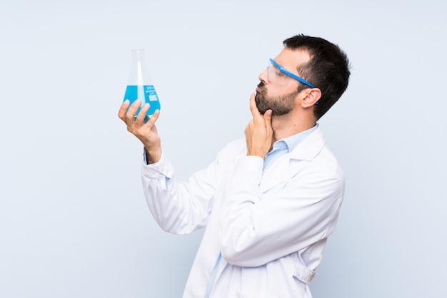 孤立した壁の上の若い科学持株実験室のフラスコ