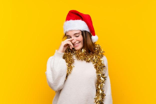 笑っている孤立した黄色の壁の上のクリスマス帽子の少女