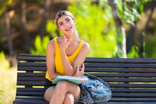見上げながらアイデアを考えて屋外で学生の女の子