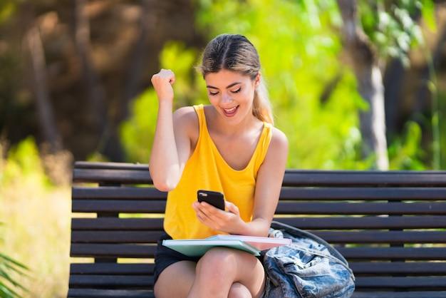 驚いたとメッセージを送信する屋外で学生の女の子