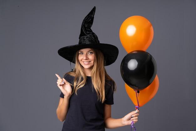 Молодая ведьма держит черные и оранжевые воздушные шарики, указывая пальцем в сторону