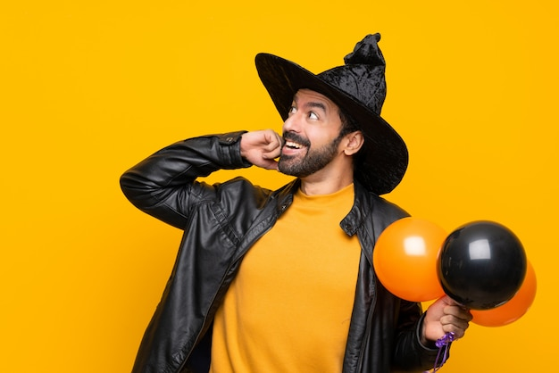 Человек с шляпой ведьмы держит черные и оранжевые воздушные шарики для вечеринки в честь хэллоуина думая идею