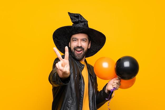 Человек с шляпой ведьмы держит черные и оранжевые воздушные шары для хэллоуина, улыбаясь и показывая знак победы