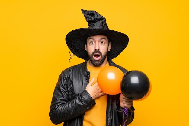 Человек в шляпе ведьмы держит черные и оранжевые воздушные шарики для хэллоуина удивлен и шокирован, глядя прямо