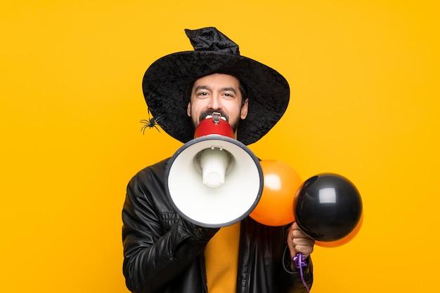 メガホンを通して叫ぶハロウィーンパーティーの黒とオレンジの気球を保持している魔女の帽子を持つ男