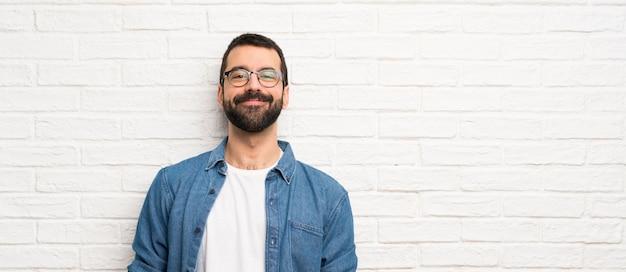 白いレンガの壁の笑いでひげを持つハンサムな男