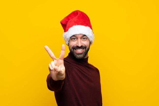 Человек с шляпой рождества над изолированной желтой стеной усмехаясь и показывая знак победы