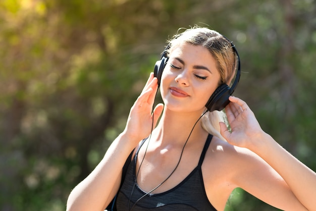 ヘッドフォンで音楽を聞いて屋外でスポーツをするスポーツ少女