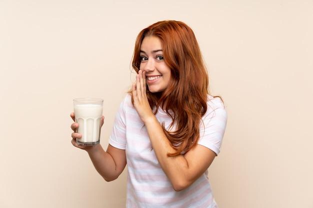 Рыжая девушка подросток держит стакан молока над изолированной стеной шепчет что-то