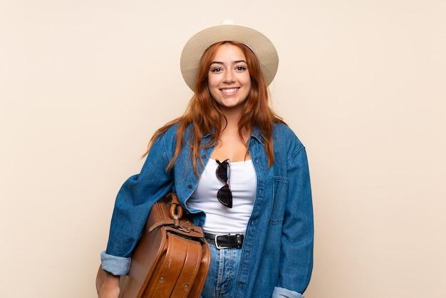 多くの笑みを浮かべて孤立した壁の上のスーツケースで赤毛の旅行者の女の子