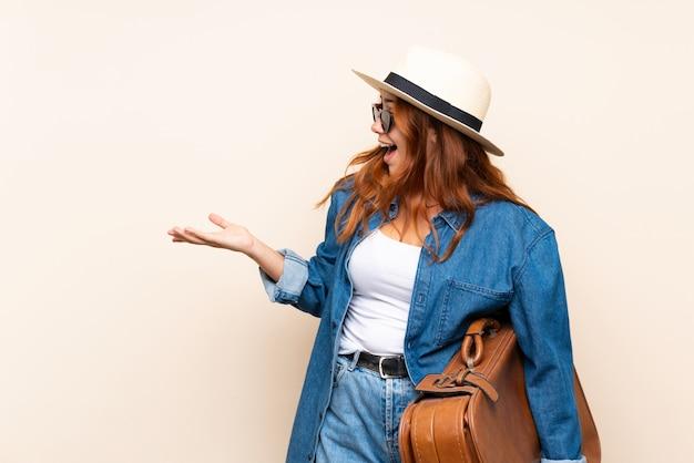 驚きの表情で孤立した壁の上のスーツケースで赤毛の旅行者の女の子