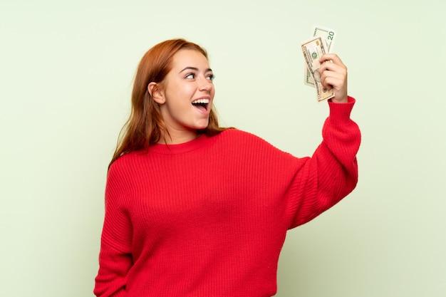 たくさんのお金を取って孤立した緑の壁の上のセーターとティーンエイジャーの赤毛の女の子