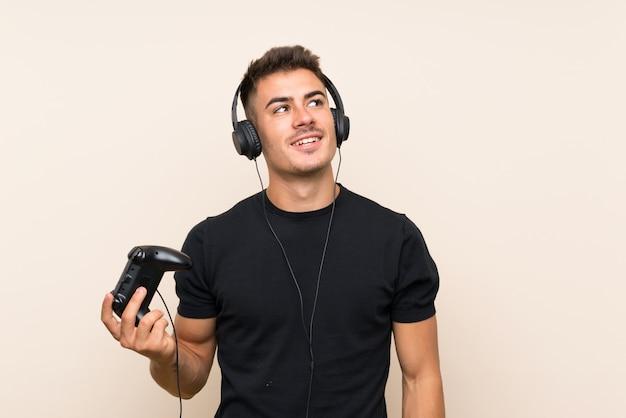 Молодой красавец, играя с контроллером видеоигры над изолированной стеной, глядя вверх, в то время как улыбается