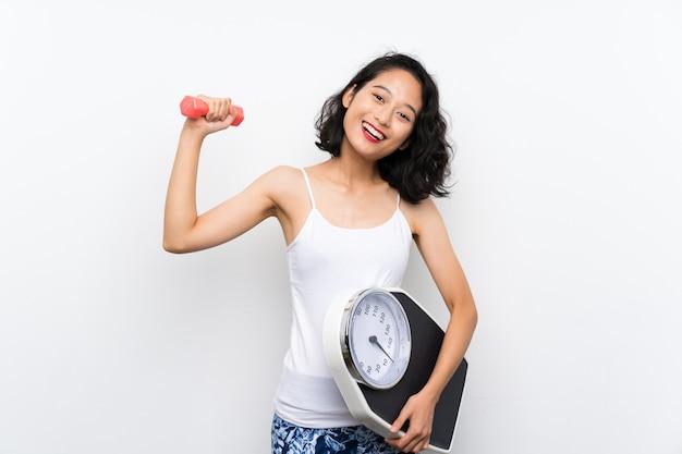 重量挙げと計量機で若いアジアの女の子
